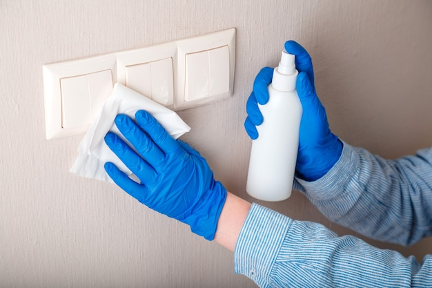 表面消毒。ゴム製の青い手袋をはめた家事労働者は、アルコールスプレーとぼろきれで壁に布を付けて光のスイッチをきれいにします。新しい通常のcovid 19コロナウイルスの消毒、家の掃除。