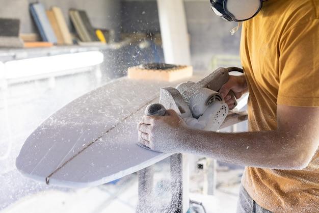 サンダーでサーフボードを形作るサーフボードモデリングワークショップの男