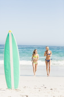 Surfboard in sand and two women running on the beach