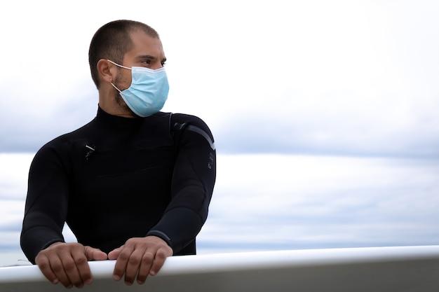 サーフボードサーファー、マスクの男とビーチのウェットスーツ