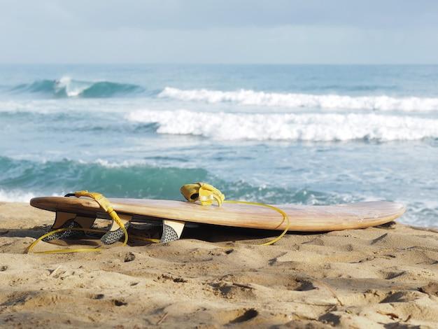 Доска для серфинга с желтым поводком на песке.