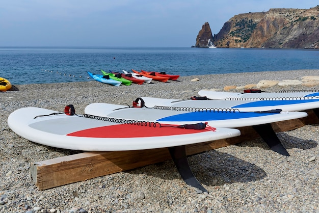 Surfboards on the coast with kayaks on the background of the sea and rocks.