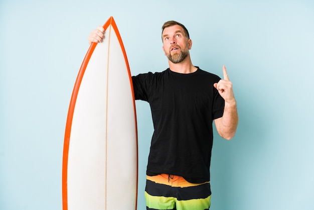 Surfen man isolated on blue background pointing upside with opened mouth.