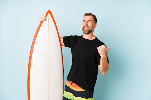 Surfen man isolated on blue wall points with thumb finger away, laughing and carefree.