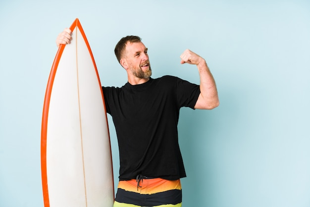 Surfen man isolated on blue wall raising fist after a victory, winner concept.