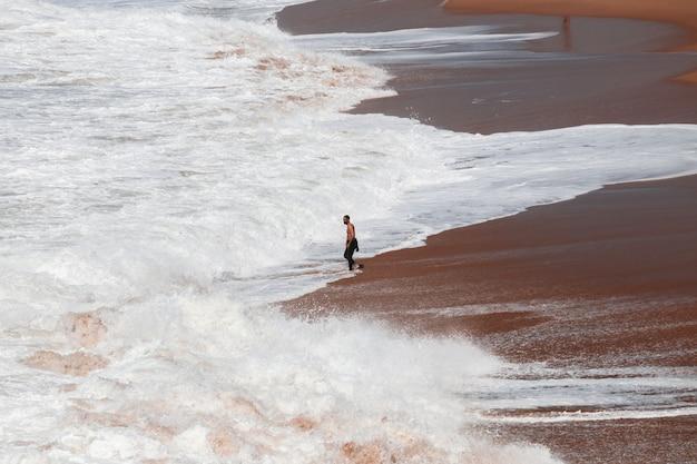 Surfer on the coast between crashing waves in cadiz, spain