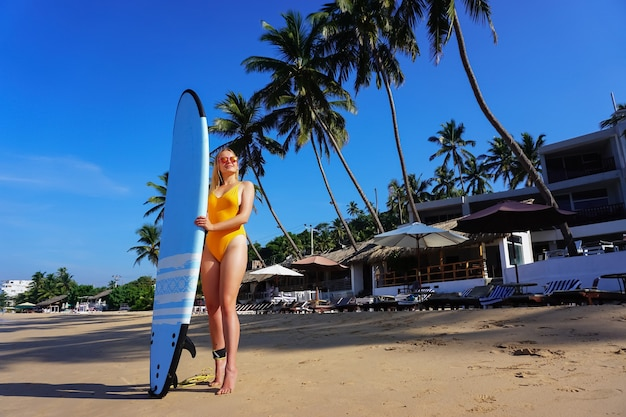 Surfer girl on the beach with palm trees