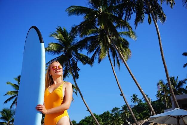 Серфер девушка на пляже в солнцезащитных очках