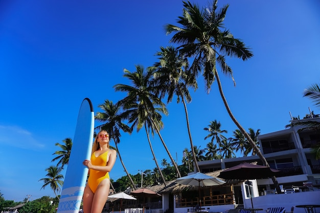 Серфер девушка позирует с доской для серфинга