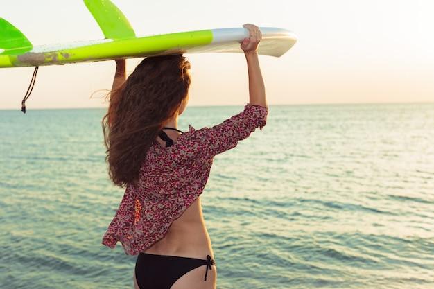Surfer girl surfing looking at ocean beach sunset