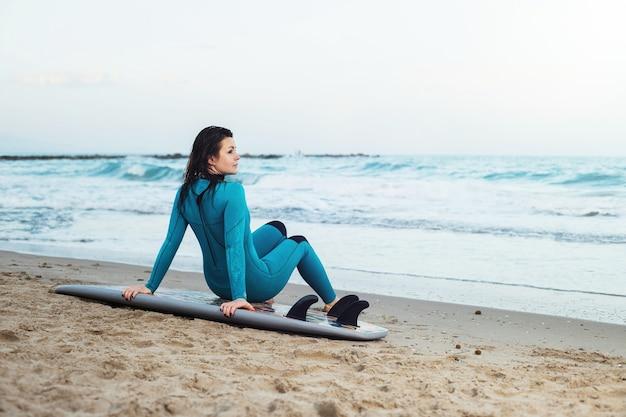 모래 해변에서 보드와 함께 산책하는 서퍼 소녀. 서퍼 여성 해변에서 아름 다운 젊은 여자.