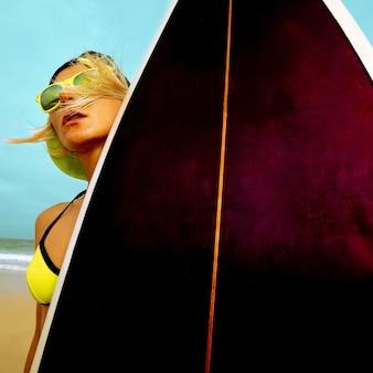 ビーチでスタイリッシュなサーフボードを持つサーファーガール。サーフィンタイム