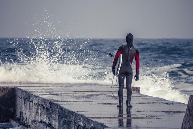 Зимой серфер заходит в воду в гидрокостюме. холодный серфинг. всплеск волны. водонепроницаемый костюм