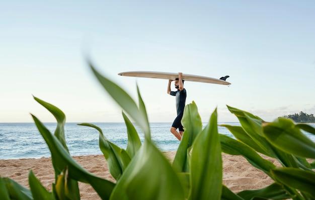 Surfer e la sua tavola da surf a lungo raggio