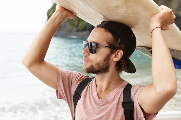 夏休みのサーファーライフスタイル。サーフィンに行くサングラスをかけている若い魅力的でハンサムな日焼けした白人選手の肖像画を間近します。