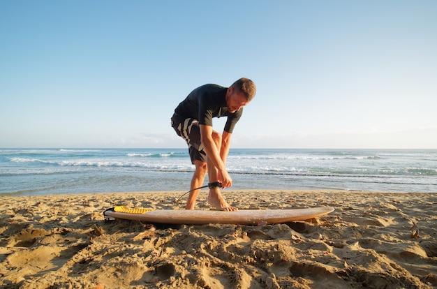 서퍼 남자는 바다에서 서핑하려고 다리에 가죽 끈을 고정합니다.