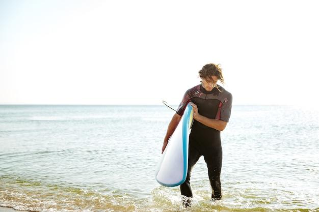 그의 손에 서핑 보드와 함께 물 밖으로 걸어 수영복에 서퍼 남자