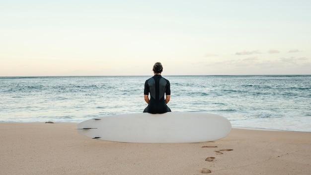 Серфер человек смотрит на море горизонтальный длинный план