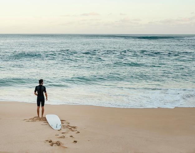 Uomo del surfista che esamina il colpo lungo orizzontale del mare