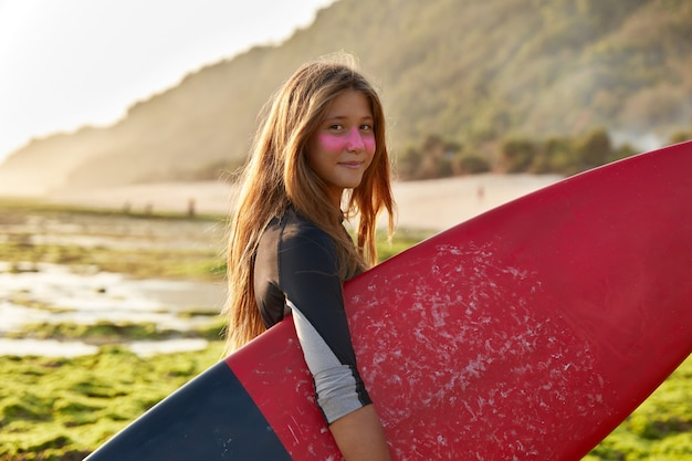 Surfer and ocean concept. delighted dark haired woman carries waxed surfboard looks with satisfied expression