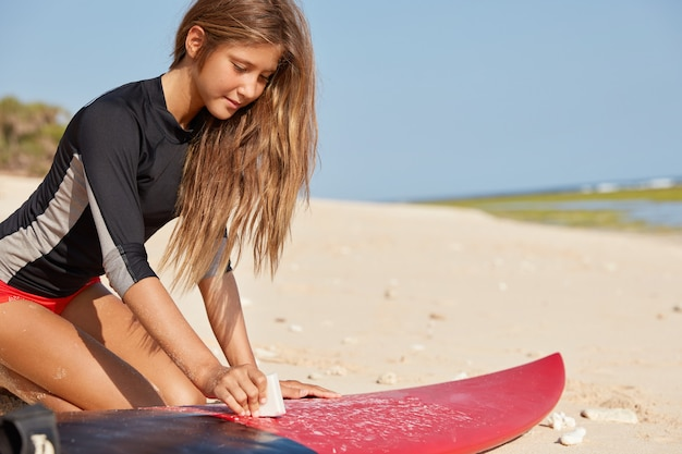 Surfista e oceano. immagine ritagliata della ragazza attiva vestita in costume da bagno, si siede sulla sabbia calda