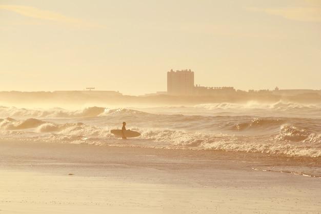 Surfer in ocean in sunset