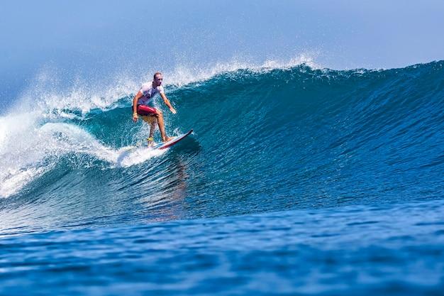 Серфер на удивительной голубой волне, остров бали.