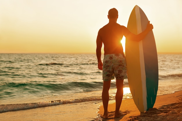 Серфер на берегу океана на закате
