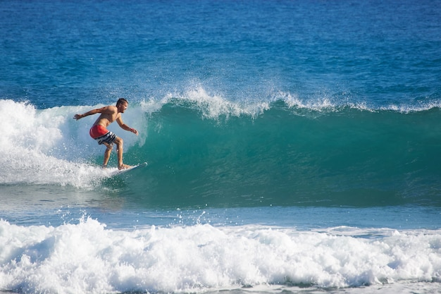 Surfer riding fast on perfect tropical blue wave. men catching waves in ocean.
