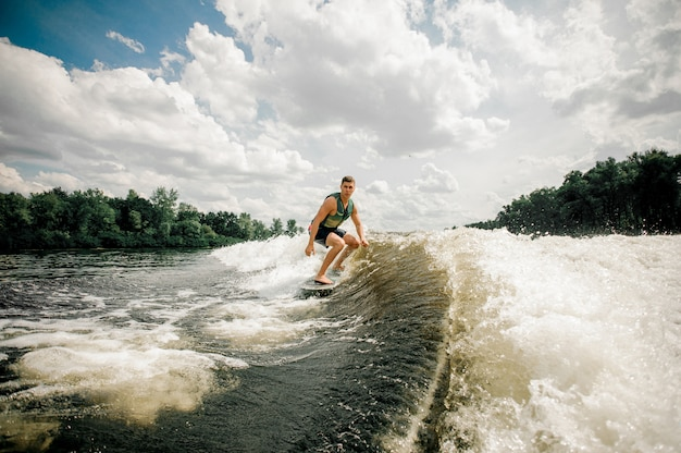 Surfer riding wakeboard on high wave, having extreme summertime