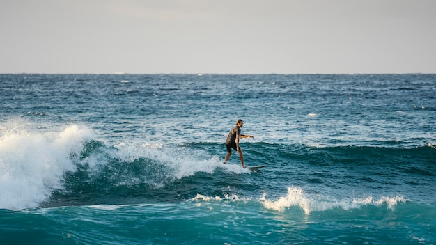 Surfer riding wave in daylight long view