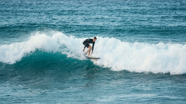Surfer riding wave in daylight