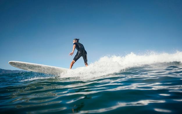 日中のロングビューで波に乗るサーファー