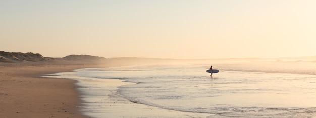 日の出のビーチで走っているサーファー