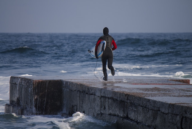 Зимой серфер бежит в воду в гидрокостюме. холодный серфинг. всплеск волны. водонепроницаемый костюм