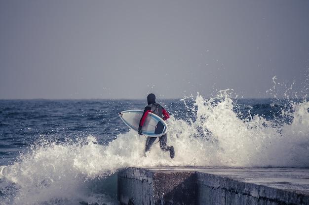 Зимой серфер бежит в воду в гидрокостюме. холодный серфинг. всплеск волны.