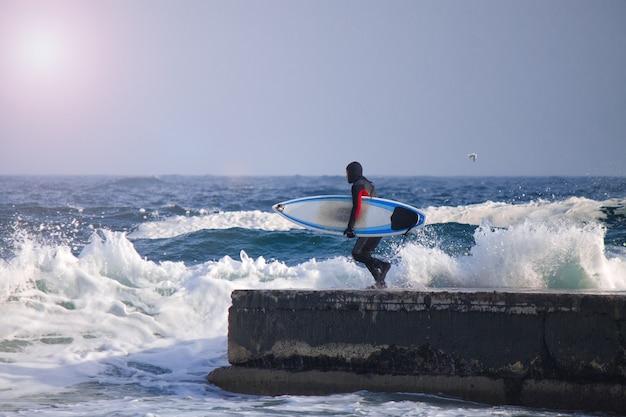 Серфер в гидрокостюме бежит в воду. всплеск волны. водонепроницаемый костюм