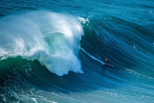 Surfer sailing through the foamy waves of the atlantic ocean toward the shore of nazare