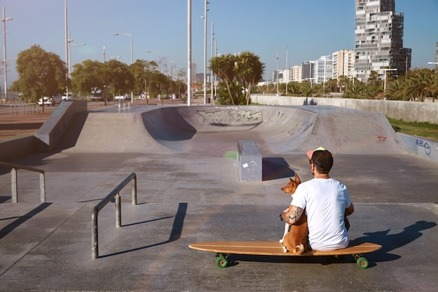 Surfer sits on a longboard in a city skatepark hugging his brown and white basenji dog, looking on city landscape, shot from the back
