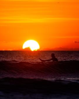 日没時に海に座っているサーファー
