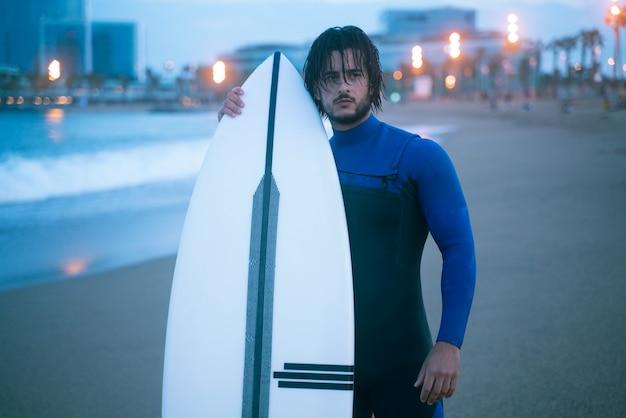 バルセロナのビーチでサーフィンの準備ができている彼のサーフボードを立って保持しているサーファー