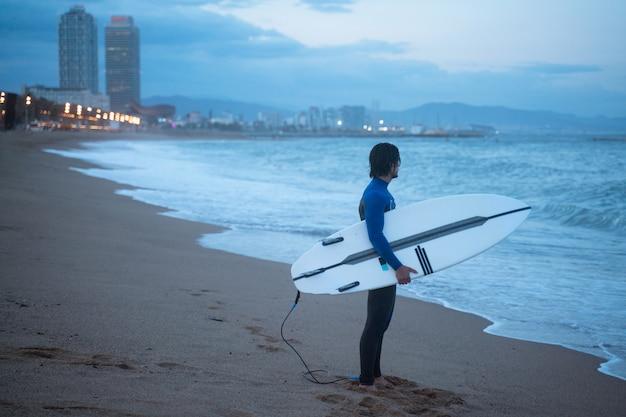 バルセロナのビーチでサーフィンの準備ができているサーフボードを立って保持しているサーファー