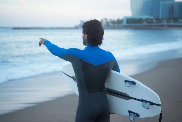 ビーチに立って、手で波を指しているサーフボードを持っているサーファー