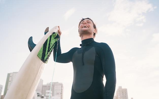 Серфер стоит на пляже с доской для серфинга