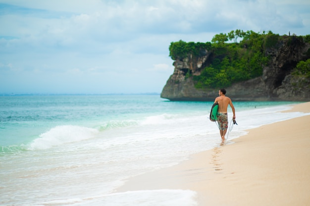 サーファー。砂浜の熱帯のビーチの上を歩いてサーフボードでサーフィン男。
