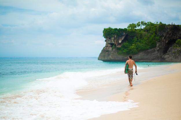 Серфер. серфинг человек с доской для серфинга, идущий на песчаном тропическом пляже.