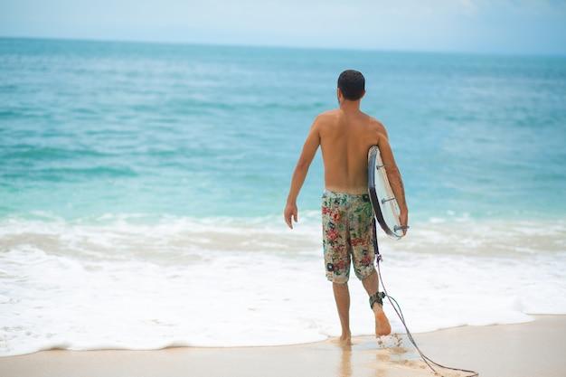 Серфер. серфинг человек с доской для серфинга, прогулки на песчаном тропическом пляже