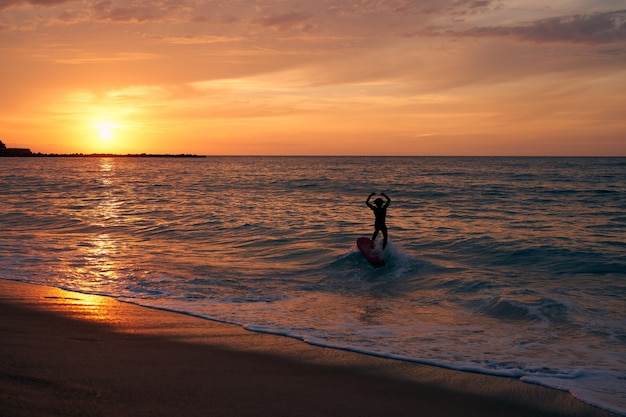 Surfer surfing a wave with the sun setting