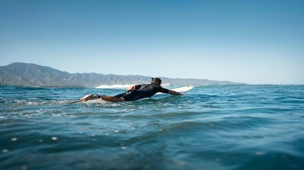 물 긴 샷에서 수영하는 서퍼