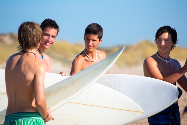 Surfer teen boys talking on beach shore